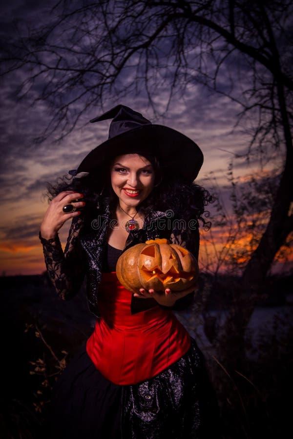 Μάγισσα αποκριών που κρατά μια κολοκύθα στοκ φωτογραφία με δικαίωμα ελεύθερης χρήσης