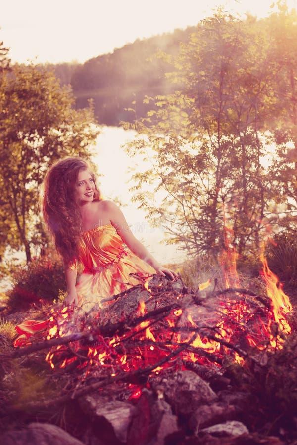 Μάγισσα ομορφιάς στα ξύλα κοντά στην πυρκαγιά Μαγικός εορτασμός γυναικών στοκ φωτογραφία