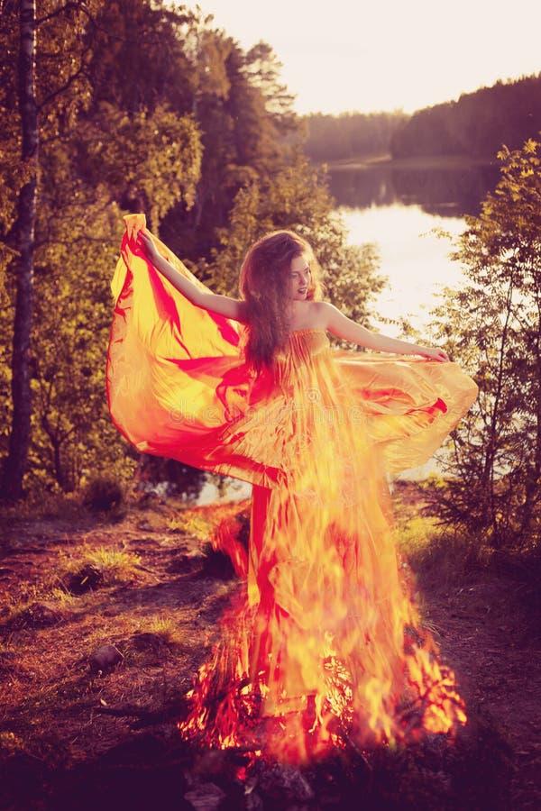 Μάγισσα ομορφιάς στα ξύλα κοντά στην πυρκαγιά Μαγικός εορτασμός γυναικών στοκ φωτογραφίες