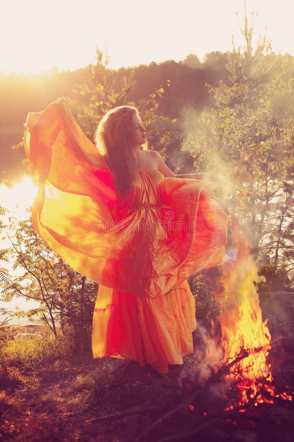 Μάγισσα ομορφιάς στα ξύλα κοντά στην πυρκαγιά Μαγικός εορτασμός γυναικών στοκ εικόνα