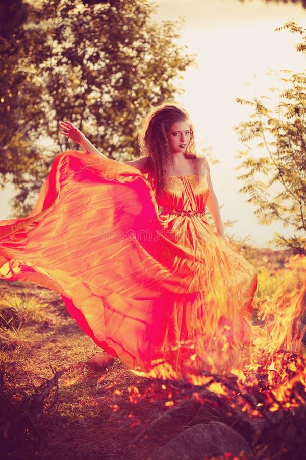 Μάγισσα ομορφιάς στα ξύλα κοντά στην πυρκαγιά Μαγικός εορτασμός γυναικών στοκ εικόνες
