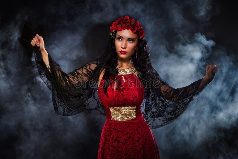 Μάγισσα στο κόκκινο φόρεμα στοκ εικόνα