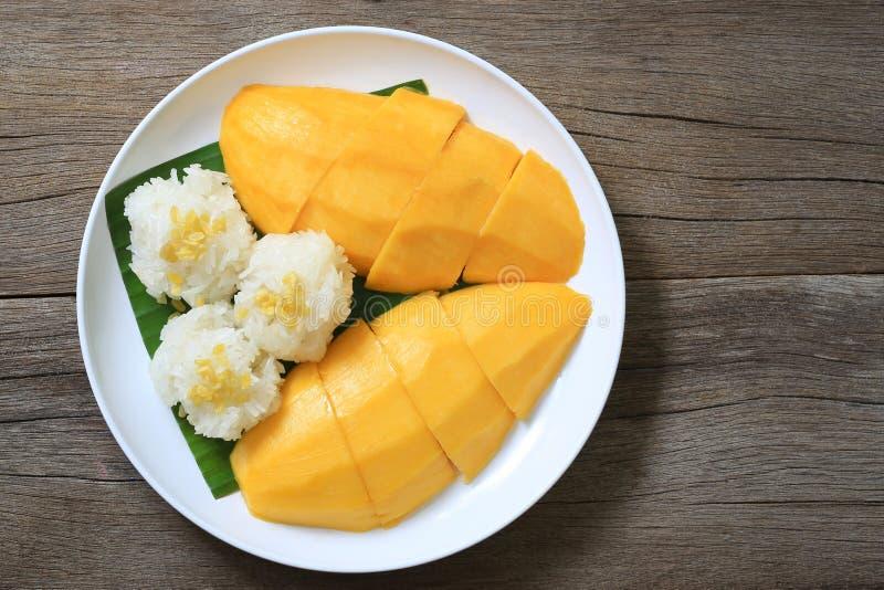 Μάγκο και κολλώδες ρύζι στο άσπρο πιάτο στο ξύλινο πάτωμα, ταϊλανδικά des στοκ εικόνες