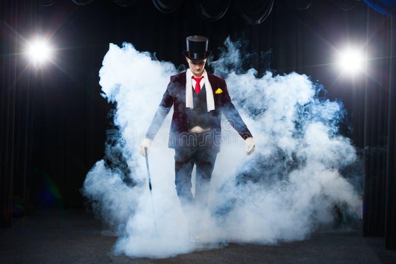 Μάγος, άτομο ζογκλέρ, αστείο πρόσωπο, μαύρος μαγικός, παραίσθηση που στέκεται στο στάδιο με έναν κάλαμο του όμορφου φωτός στοκ φωτογραφίες