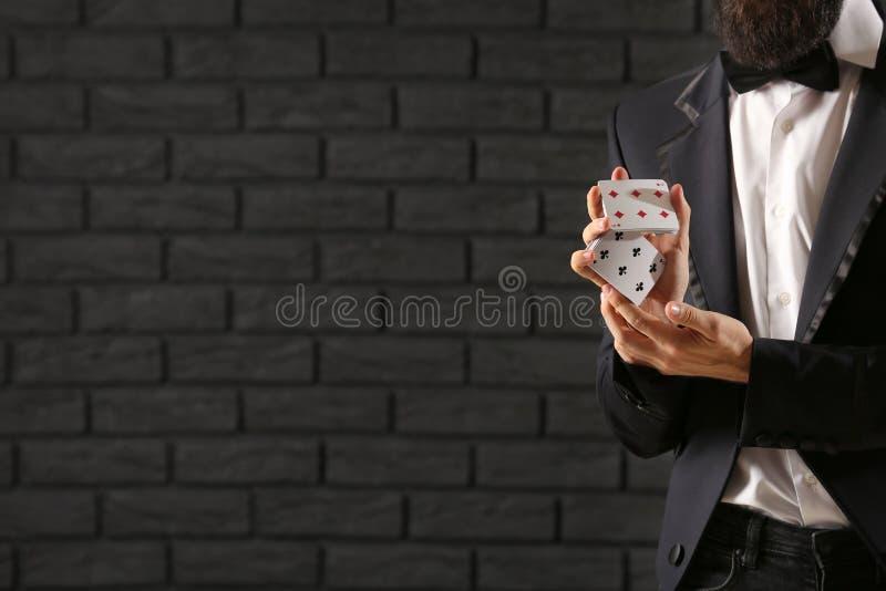Μάγος με τις κάρτες ενάντια στο σκοτεινό τουβλότοιχο στοκ εικόνες