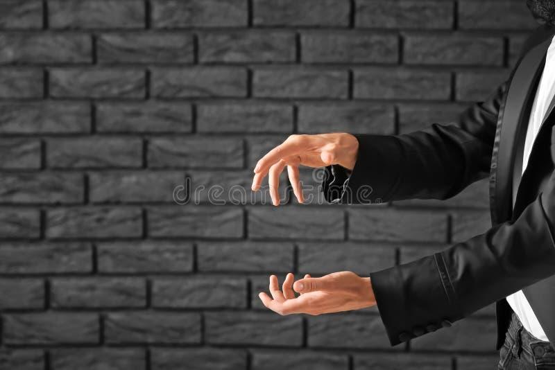 Μάγος που παρουσιάζει τεχνάσματα ενάντια στο σκοτεινό τουβλότοιχο στοκ φωτογραφίες με δικαίωμα ελεύθερης χρήσης