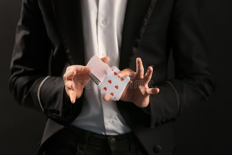 Μάγος που παρουσιάζει τεχνάσματα με τις κάρτες στο σκοτεινό υπόβαθρο, κινηματογράφηση σε πρώτο πλάνο στοκ εικόνες με δικαίωμα ελεύθερης χρήσης