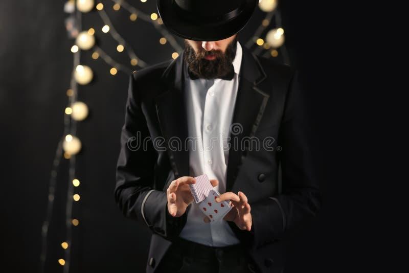 Μάγος που παρουσιάζει τεχνάσματα με τις κάρτες στο σκοτεινό υπόβαθρο στοκ εικόνα