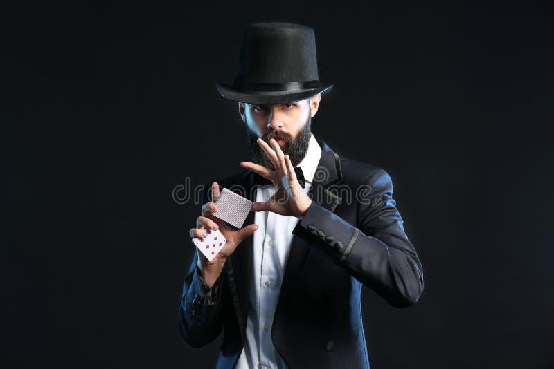 Μάγος που παρουσιάζει τεχνάσματα με τις κάρτες στο σκοτεινό υπόβαθρο στοκ φωτογραφίες με δικαίωμα ελεύθερης χρήσης