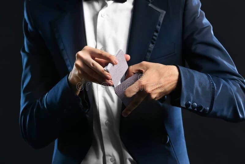Μάγος που παρουσιάζει τεχνάσματα με τις κάρτες στο σκοτεινό υπόβαθρο, κινηματογράφηση σε πρώτο πλάνο στοκ εικόνα με δικαίωμα ελεύθερης χρήσης