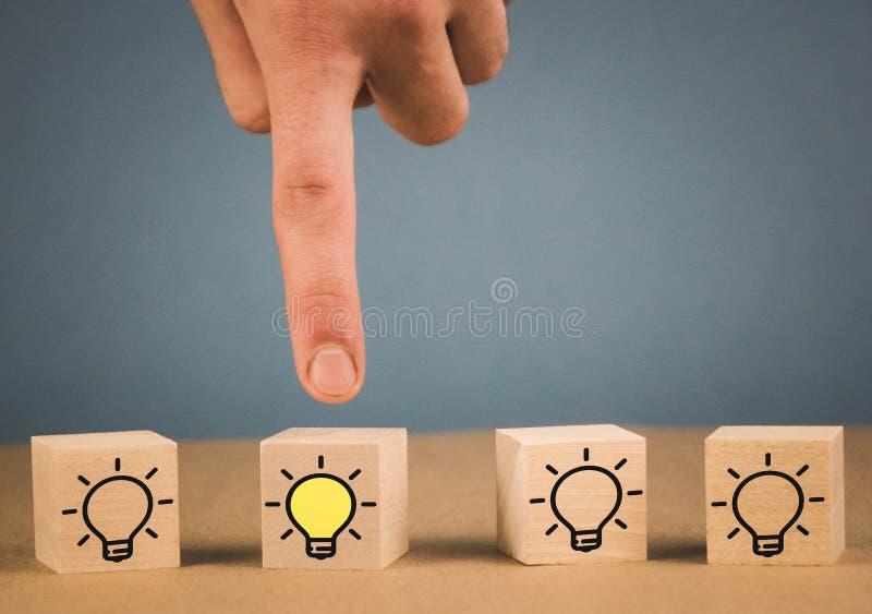 Μάζεψε με το χέρι τους ξύλινους κύβους με το κίτρινο σύμβολο λαμπών φωτός στο μπλε υπόβαθρο Νέες ιδέα, καινοτομία και λύση στοκ εικόνες