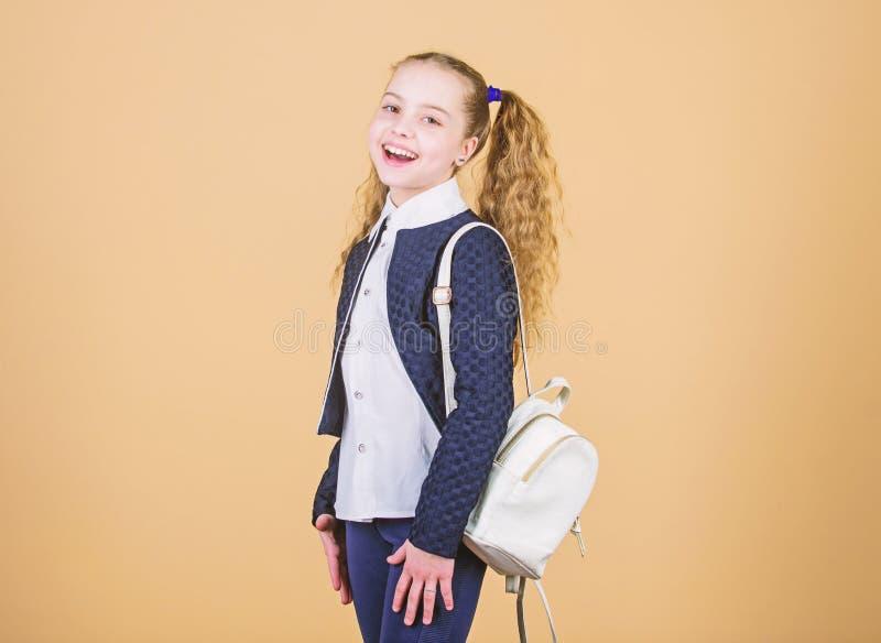 Μάθετε πώς κατάλληλο σακίδιο πλάτης σωστά Το κορίτσι λίγο μοντέρνο cutie φέρνει το σακίδιο πλάτης Δημοφιλές χρήσιμο εξάρτημα μόδα στοκ φωτογραφία
