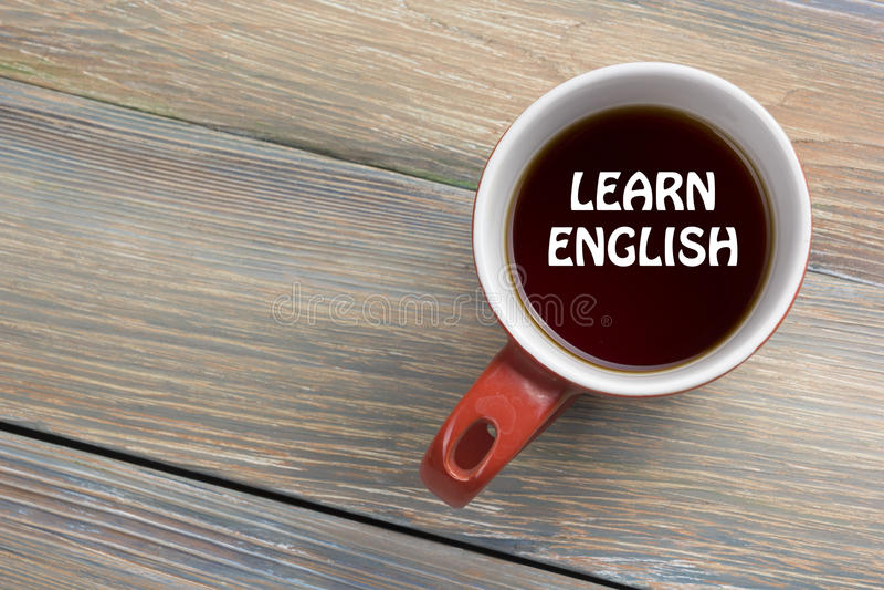 Μάθετε το αγγλικό κείμενο που γράφεται στο φλυτζάνι καφέ Άποψη επιτραπέζιων κορυφών γραφείων γραφείων στοκ φωτογραφία με δικαίωμα ελεύθερης χρήσης