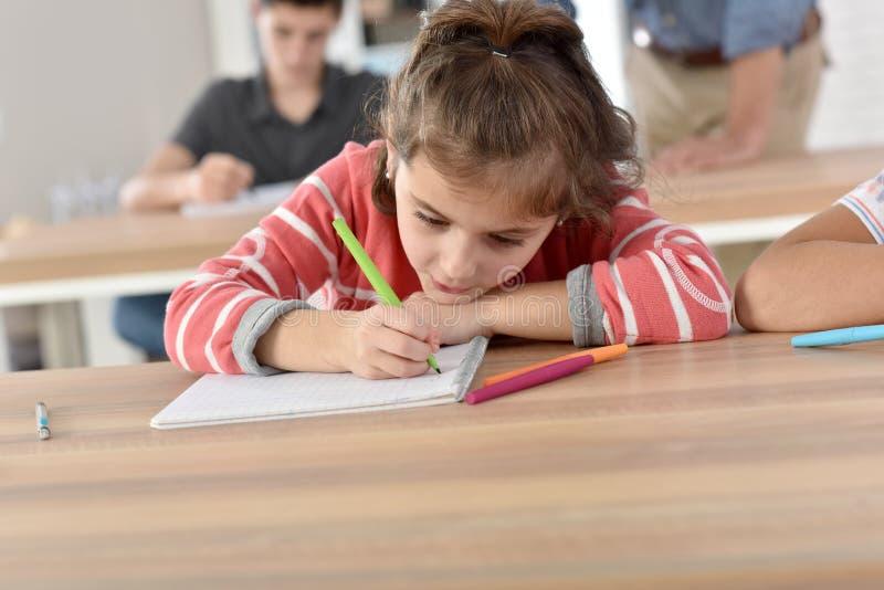 Μάθημα γραψίματος μαθητριών στο σημειωματάριο στοκ εικόνα
