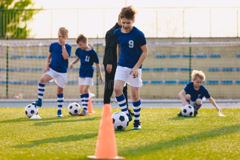 Μάθημα φυσικής αγωγής ποδοσφαίρου Παιδιά που εκπαιδεύουν το ποδόσφαιρο στο σχολικό τομέα στοκ φωτογραφίες με δικαίωμα ελεύθερης χρήσης