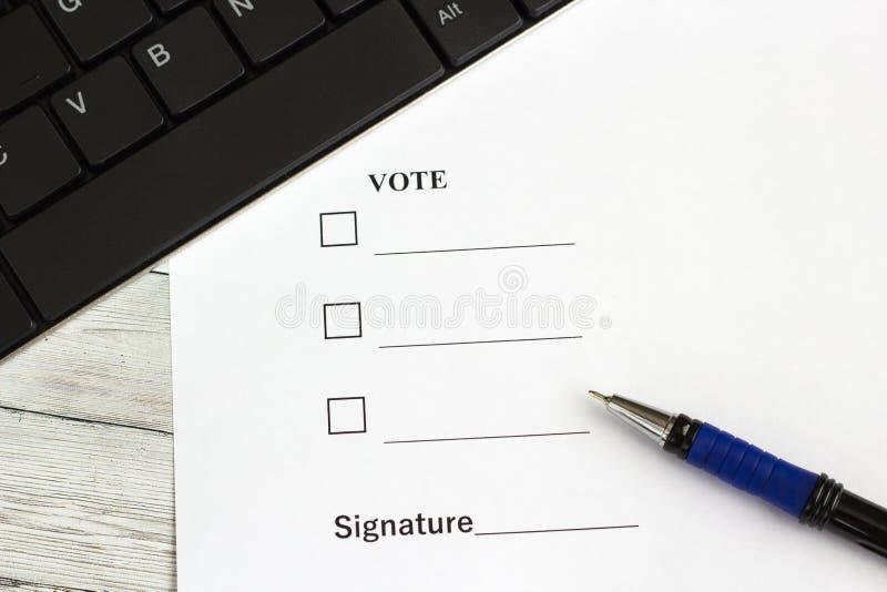 Μάνδρα για το γράψιμο στον ξύλινο πίνακα με ένα έγγραφο για την ψηφοφορία και το πληκτρολόγιο στοκ εικόνες
