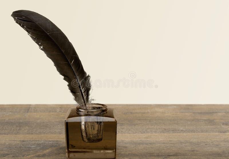 Μάνδρα και γυαλί καλαμιών φτερών inkwell στον πίνακα στοκ φωτογραφίες