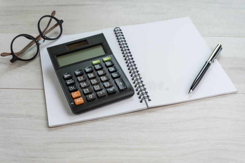 Μάνδρα και υπολογιστής στο άσπρο σημειωματάριο με eyeglasses που χρησιμοποιούν ως Bu στοκ εικόνα