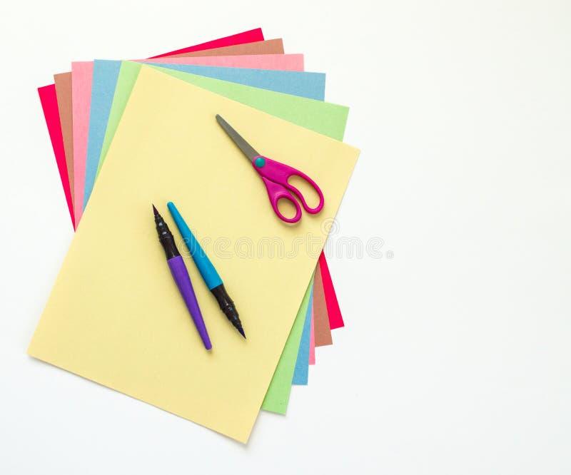 Μάνδρες ψαλιδιού και χρωμάτων παιδιών ` s πάνω από το αερισμένο έξω έγγραφο κατασκευής που απομονώνεται στο λευκό στοκ εικόνα