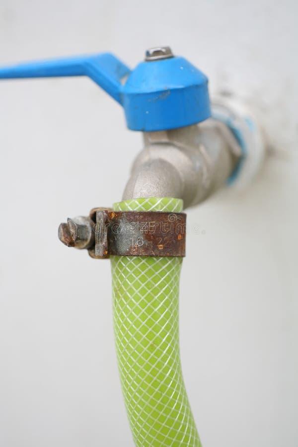 Μάνικα νερού με το σκουριασμένο tightener με την μπλε λαβή στον άσπρο τοίχο στοκ εικόνα με δικαίωμα ελεύθερης χρήσης