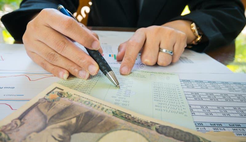 Μάνδρα λαβής χεριών επιχειρησιακών γυναικών και σημείο στη δήλωση ή την οικονομική έκθεση και χρήματα της Ιαπωνίας στην επιχειρησ στοκ φωτογραφίες