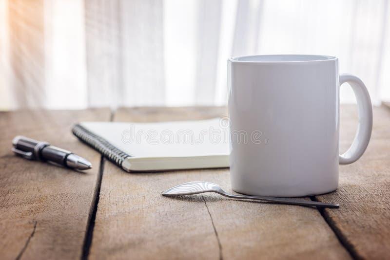 Μάνδρα και σημειωματάριο με το φλυτζάνι καφέ σε ξύλινο στοκ εικόνες