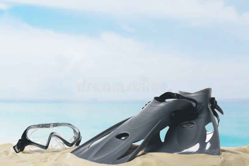 Μάσκα και βατραχοπέδιλα στην άμμο στο μπλε στοκ φωτογραφία