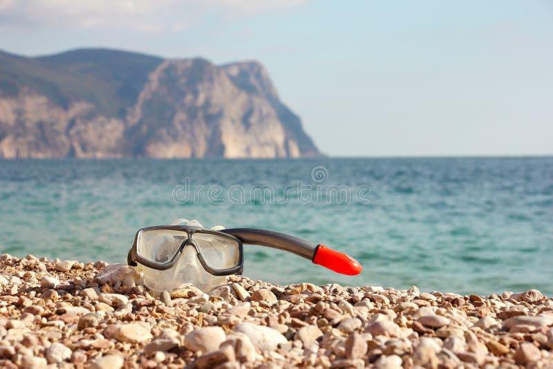 Μάσκα κατάδυσης στην παραλία πετρών με το όμορφες βουνό και τη θάλασσα backg στοκ εικόνες