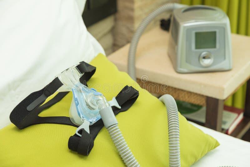 Μάσκα καλυμμάτων CPAP με τον αεροσωλήνα και μηχανή στην κρεβατοκάμαρα στοκ εικόνες