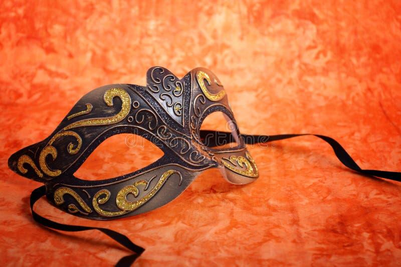 Μάσκα της Mardi Gras στο πορτοκαλί υπόβαθρο στοκ εικόνες