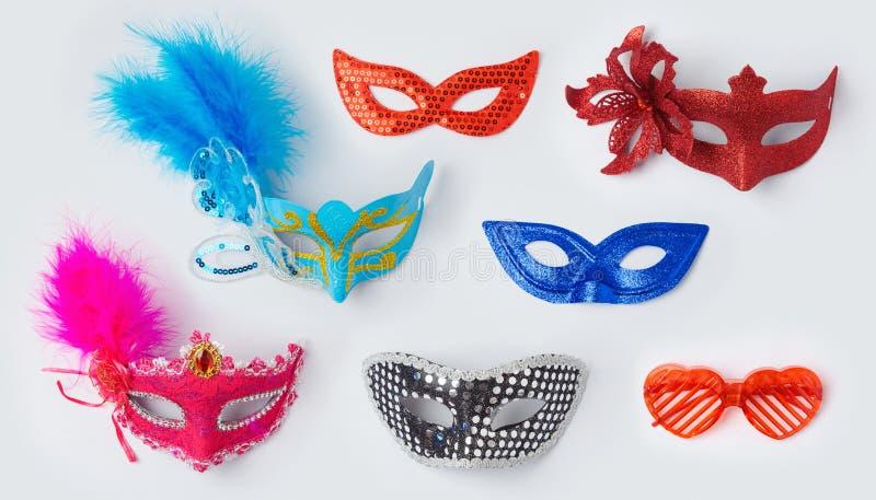 Μάσκες gras καρναβαλιού ή mardi στο άσπρο υπόβαθρο για τη χλεύη επάνω στο σχέδιο προτύπων επάνω από την όψη στοκ φωτογραφία