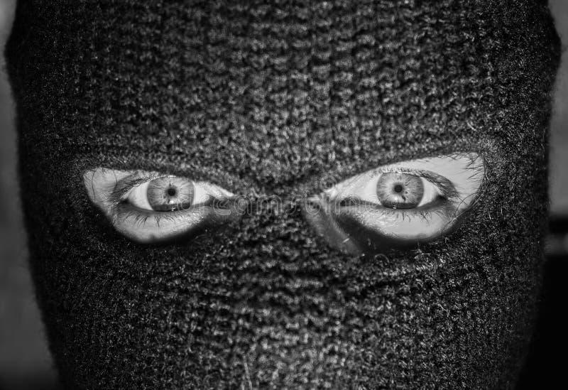 Μάτια που κοιτάζουν επίμονα από balaclava που φορά τον αριθμό στοκ εικόνα