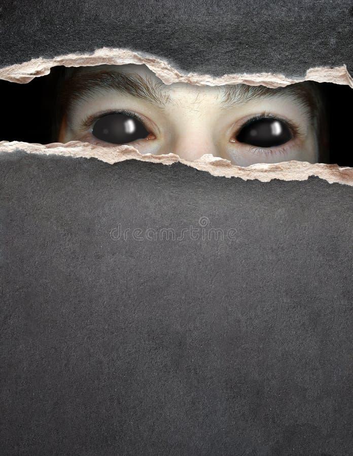 Μάτι τεράτων στην τρύπα στο έγγραφο στοκ εικόνες