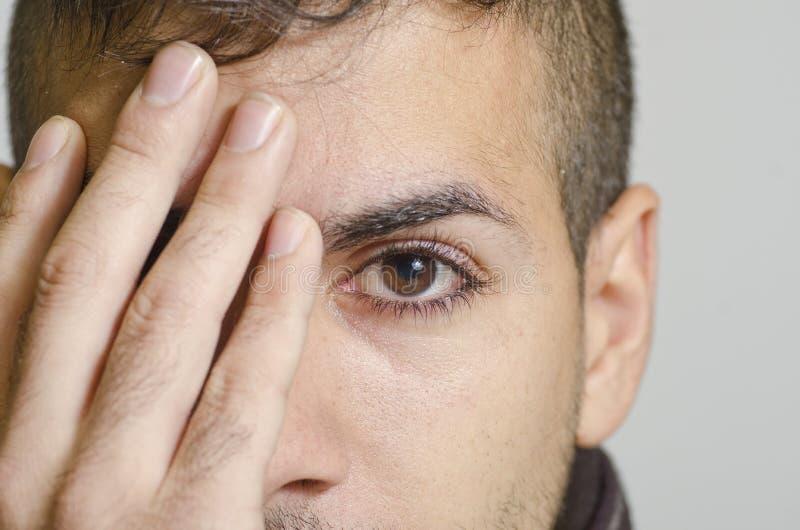 Μάτι coverin νεαρών άνδρων στοκ εικόνες με δικαίωμα ελεύθερης χρήσης