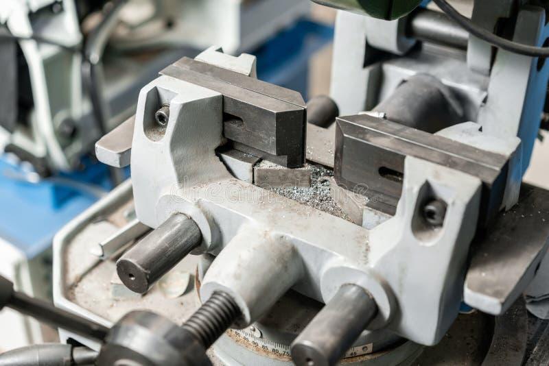 Μέγγενη για να εξασφαλίσει το κομμάτι προς κατεργασία Η εγκύκλιος είδε τη μηχανή Κόβοντας ένα μέταλλο και έναν χάλυβα με με την α στοκ φωτογραφία