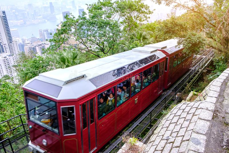 Μέγιστο τραμ Βικτώριας και μη αναγνωρισμένοι άνθρωποι με το υπόβαθρο οριζόντων πόλεων Χονγκ Κονγκ ορόσημο και προορισμός για τον  στοκ εικόνες