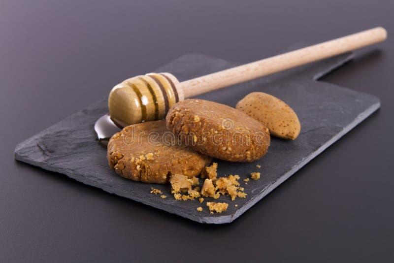 Μέλι και μπισκότα σε έναν σχιστόλιθο χαρτονιού σε ένα μαύρο υπόβαθρο στοκ εικόνα με δικαίωμα ελεύθερης χρήσης