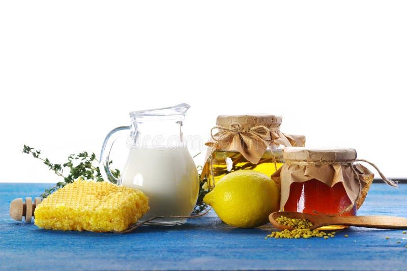 Μέλι με το γάλα και λεμόνι σε έναν μπλε παλαιό πίνακα στοκ εικόνες