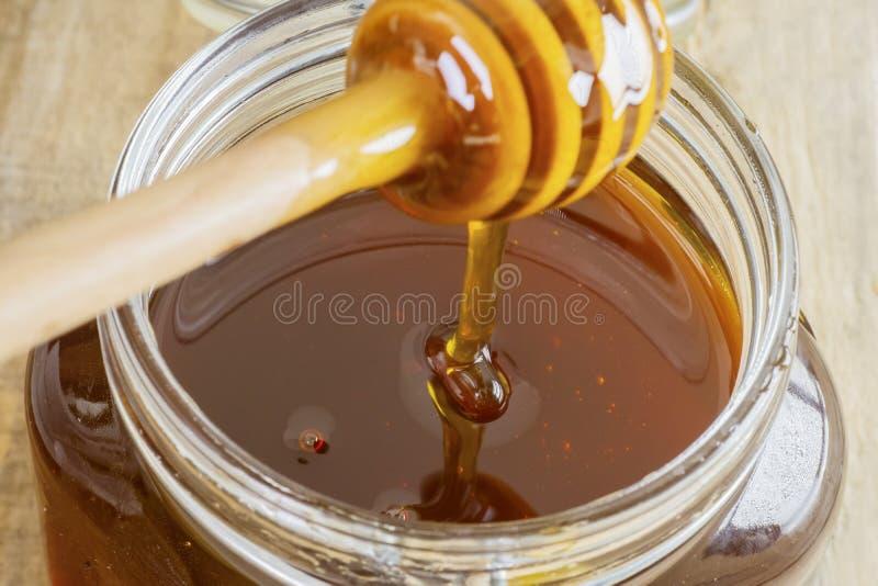 Μέλι που ρέει σε ένα βάζο γυαλιού στοκ εικόνες
