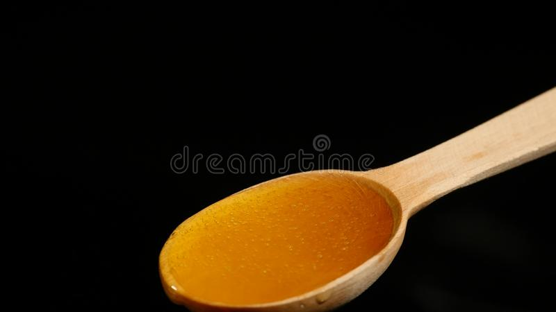 Μέλι που στάζει από ένα ξύλινο κουτάλι στο μαύρο υπόβαθρο στοκ εικόνες
