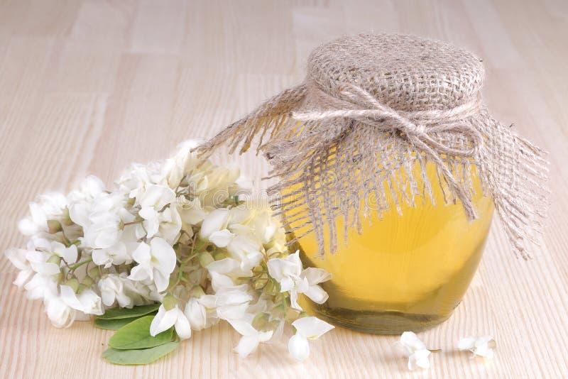 Μέλι σε ένα βάζο γυαλιού με ένα κλαδάκι της ακακίας σε ένα φυσικό ξύλινο υπόβαθρο στοκ φωτογραφία με δικαίωμα ελεύθερης χρήσης