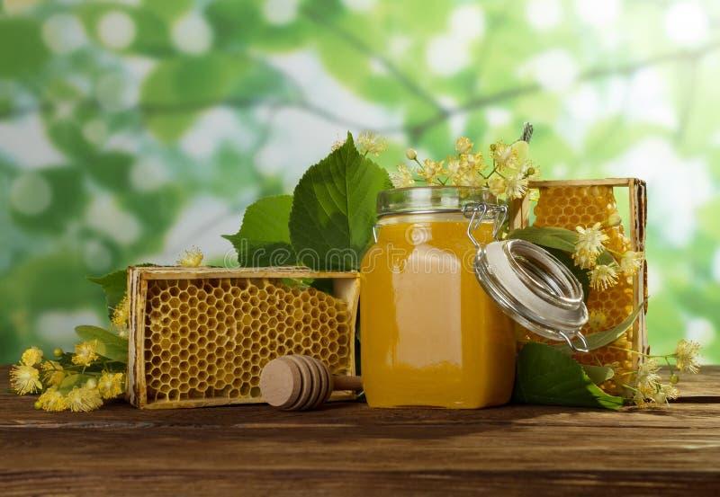 Μέλι στο βάζο με το καπάκι, κηρήθρα στον πίνακα, κινηματογράφηση σε πρώτο πλάνο στοκ εικόνα