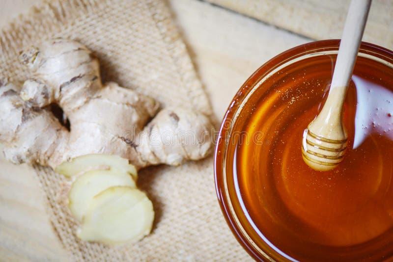 Μέλι στο βάζο με dipper μελιού και πιπερόριζα στο σάκο στον ξύλινο πίνακα στοκ εικόνα με δικαίωμα ελεύθερης χρήσης