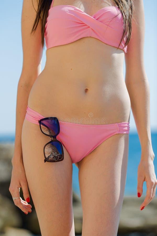 Μέλος του σώματος του κοριτσιού στο ρόδινο μπικίνι στη θάλασσα στοκ εικόνα