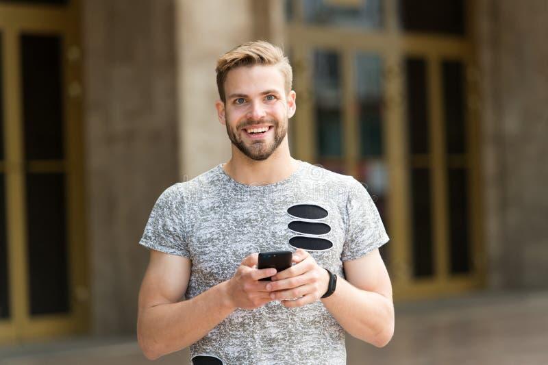 μένοντας αφή Στείλετε την έννοια μηνυμάτων Άτομο με τους περιπάτους γενειάδων με το smartphone, αστικό υπόβαθρο Smartphone χρήσης στοκ φωτογραφία με δικαίωμα ελεύθερης χρήσης