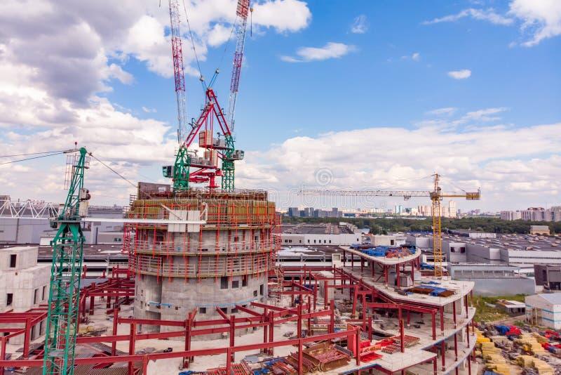 Μέρη του εργοτάξιου οικοδομής πύργων με τους γερανούς και της οικοδόμησης με το μπλε ουρανό στοκ φωτογραφία
