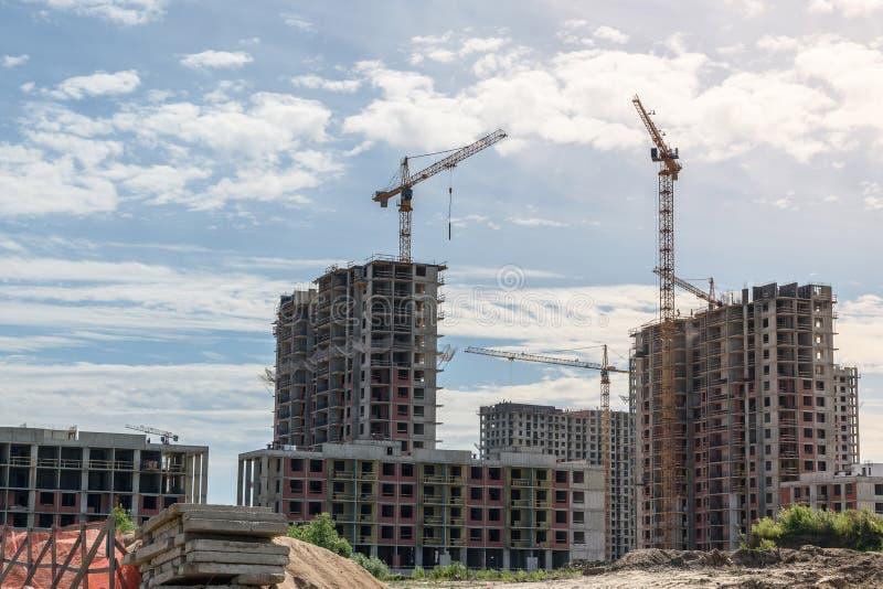 Μέρη του εργοτάξιου οικοδομής πύργων με τους γερανούς και της οικοδόμησης με το υπόβαθρο μπλε ουρανού στοκ φωτογραφία