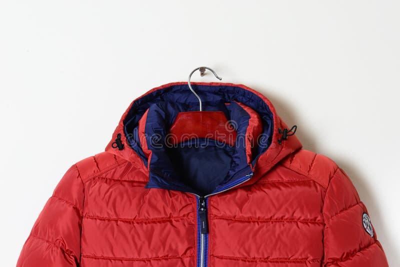 Μέρος ενός φωτεινού κόκκινου σακακιού είναι ένα κάτω σακάκι με μια κουκούλα και ένα ξεκουμπωμένο περιλαίμιο στοκ εικόνες με δικαίωμα ελεύθερης χρήσης