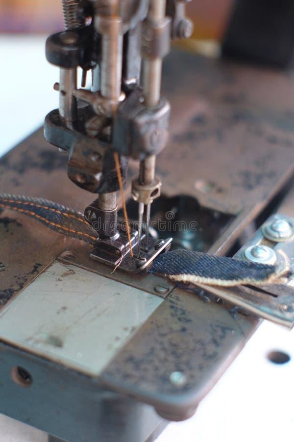 Μέρος κινηματογραφήσεων σε πρώτο πλάνο μιας παλαιών ράβοντας μηχανής και μιας λεπτομέρειας στη βελόνα & το νήμα στοκ εικόνα