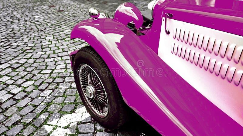 Μέρος μπροστινής πλευράς του εκλεκτής ποιότητας κλασικού πορφυρού καυτού αυτοκινήτου ράβδων σε έναν cobble δρόμο στοκ φωτογραφίες